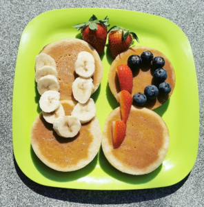 Pancakes with bananas and blueberries in the shape of UP
